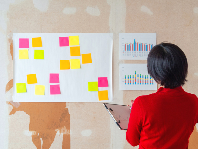 Japanese female entrepreneur stick the ideas on adhesive note in unfinished office space.