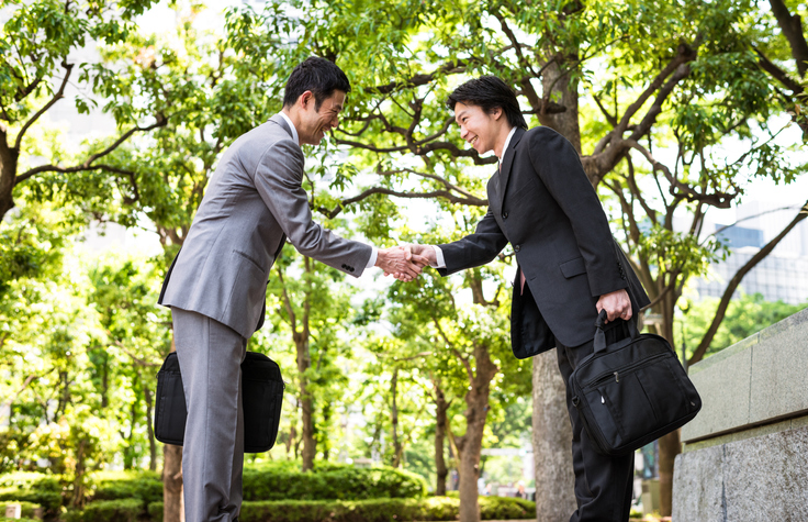 Two Japanese businessmen in Tokyo, greeting eachother with a handshake and a bow.
